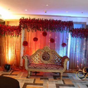 royal wedding stage, red backdrop, red flowers, wedding planner, event management company, wedding decoration