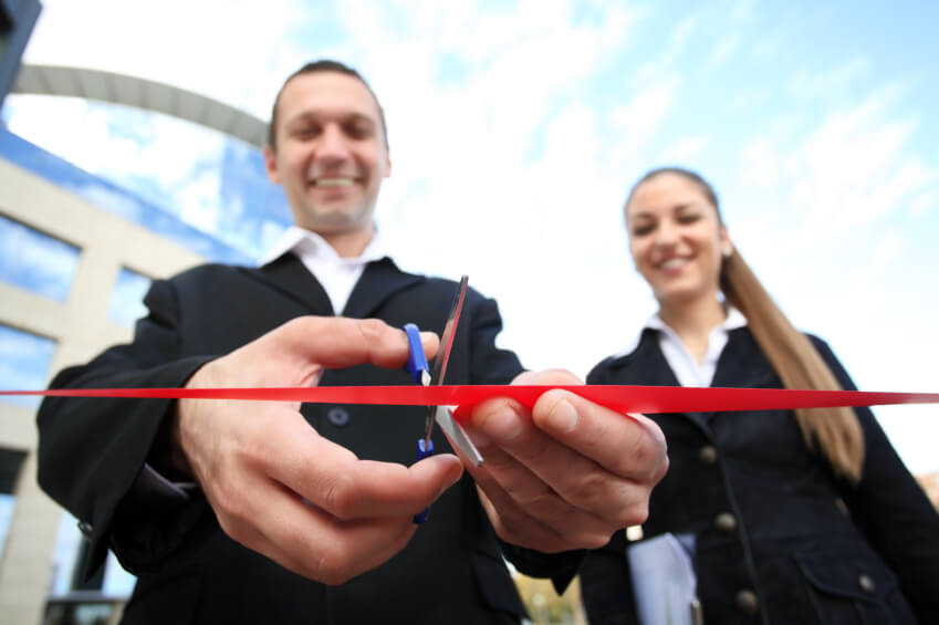 man in black suit cutting red ribbon of newly opened shop